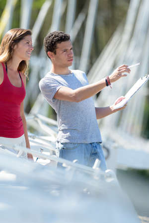 young couple in marina with clipboard