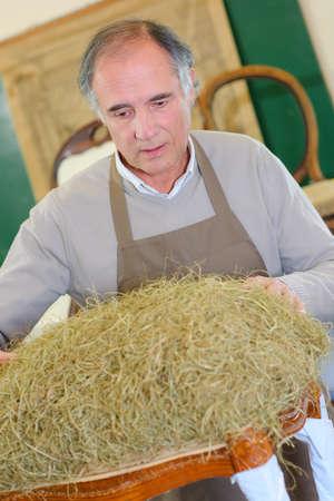 a farmer inspecting some hay Stok Fotoğraf