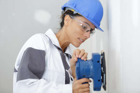 young woman is sanding wall