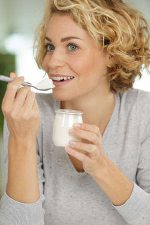 young woman with yogurt on blurred background