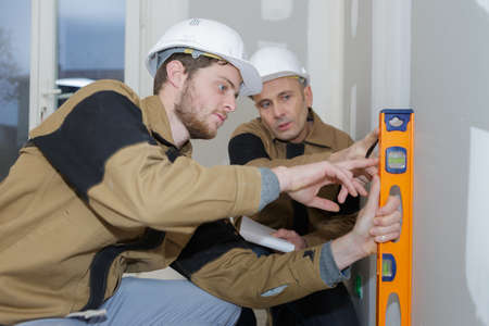 apprentice builder with foreman using spirit level on indoor worksite Stockfoto