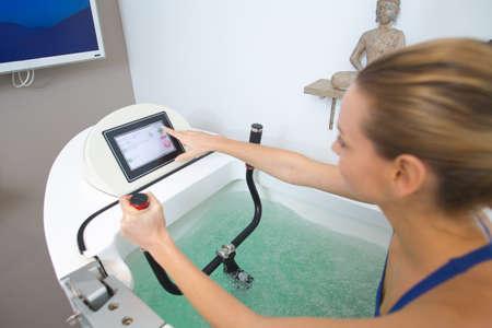 Frau im Schwimmbad macht Aquabike-Übungen