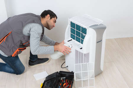 Man working on mobile air conditioning unit Stock fotó