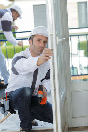 a carpenter works with drill