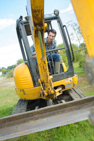 portrait of man operating a mini digger