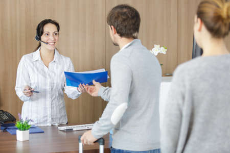 receptionist wearing headset passing file to man Stok Fotoğraf