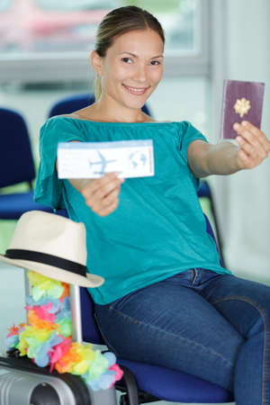 pleased lady with passport with boarding pass in hand Stok Fotoğraf