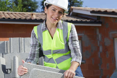 woman construction builder working with cement blocks