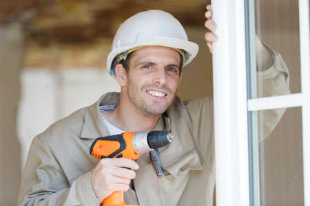 a man is drilling a window