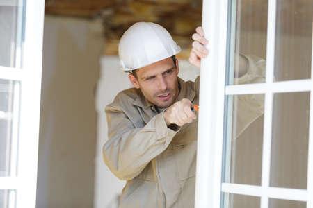 service man installing window with screwdriver Stok Fotoğraf