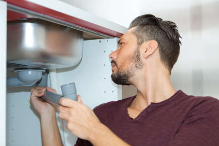young plumber working with pipe wrench in kitchen Banco de Imagens