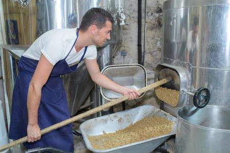 beer brewer in his brewery at food tank