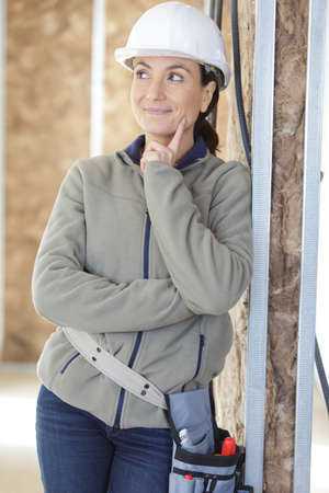 female worker posing next to wall insulation works