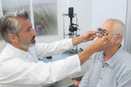 male ophthalmologist adjusting test glasses on senior male patient