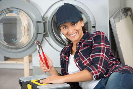 lady holding pliers to repair washing machine