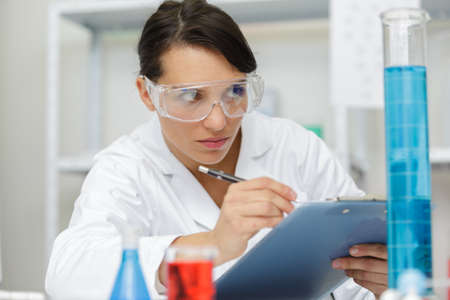 woman writing notes in lab