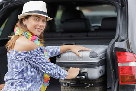woman puts luggages in the car trunk