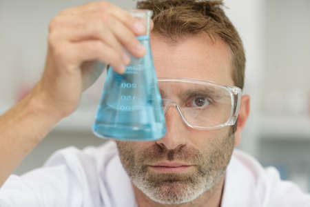male scientist examining glass flask of blue liquid