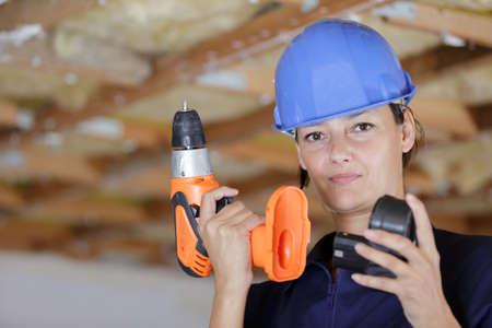 woman builder putting the driller battery