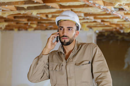 worker in overalls on mobile phone
