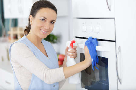 a happy lady cleaning an oven