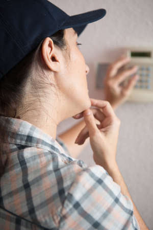 female plumber adjusting the thermostat of a gas heating 写真素材