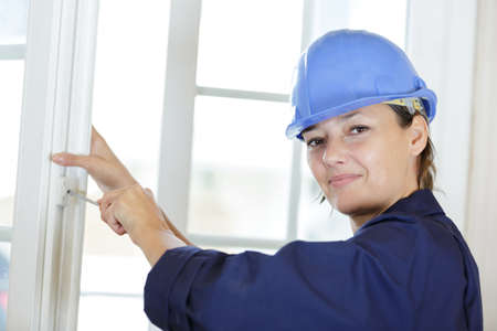 female builder tightening screw with screwdriver