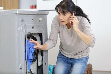 femme d'âge moyen utilisant un téléphone intelligent pour signaler des problèmes