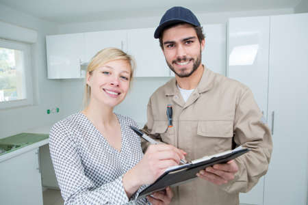 female customer signing tradesmans clipboard 写真素材