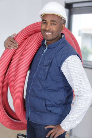 male builder carrying red pipe on his shoulder Banque d'images