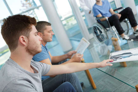 young men and one in a wheelchair in a waiting room Stok Fotoğraf