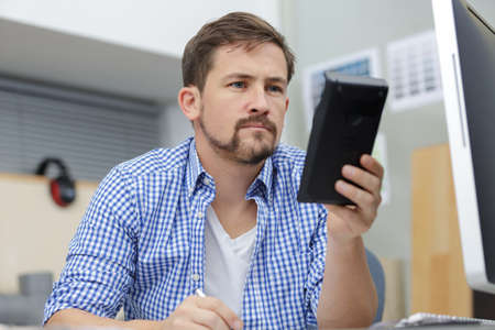 man with the calculator and computer in office