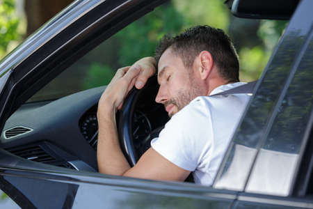 handsome man sleeping in a car