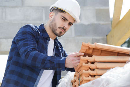male builder is checking tiles