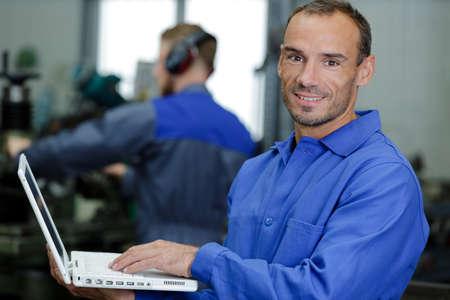 happy mechanic diagnosing car problem with computer Stock Photo