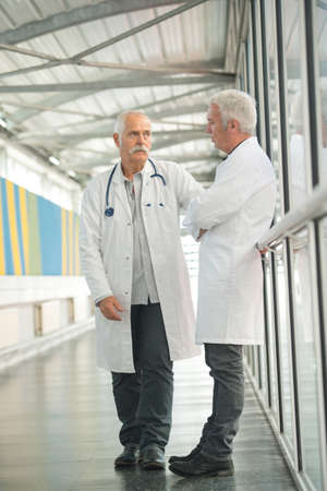 two senior doctors talking in the hospital hallway