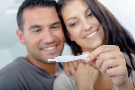 happy excited couple making positive pregnancy test