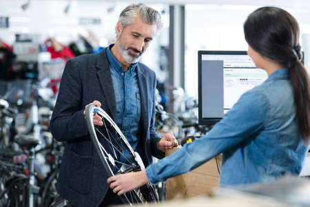 man buying a bike wheel Фото со стока