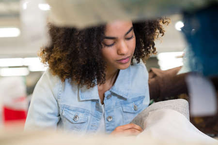 young woman working with fabric samples Stock Photo