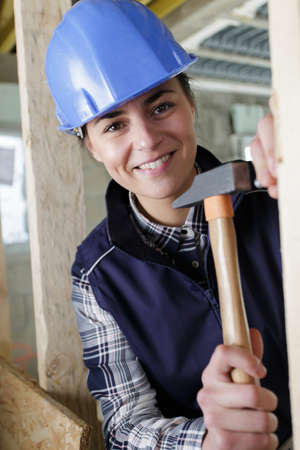 joyful experienced builder smiling while hammering a nail