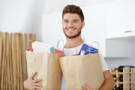 hombre sosteniendo una bolsa de papel llena de comida
