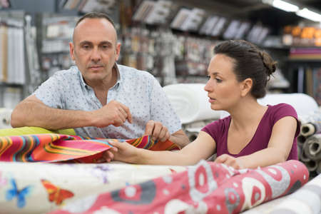 couple choosing a carpet holding up a sample swatch Stok Fotoğraf