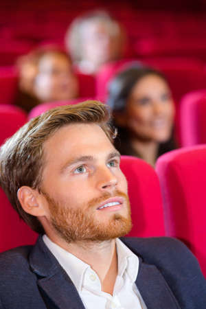 young man watching comedy in cinema hall