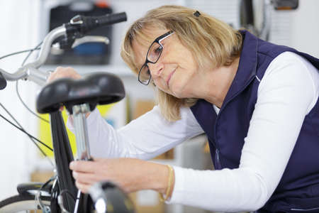 mature woman repairing a bike in workshop Reklamní fotografie