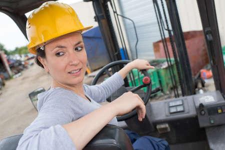 woman reversing forklift truck in scrapyard