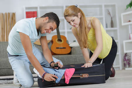 portrait of young smiling couple trying to close suitcase