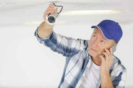 technician on the phone fixing cctv camera