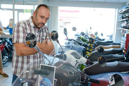 man looking at display of motorbikes Фото со стока