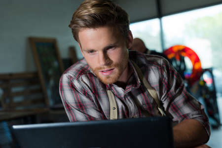young male artist using laptop Stock Photo
