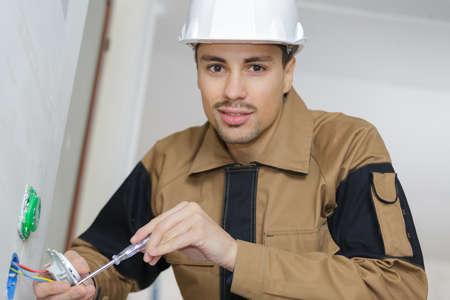 electrician mending wall plug